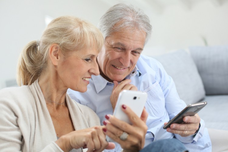 Two seniors using their smartphones at home