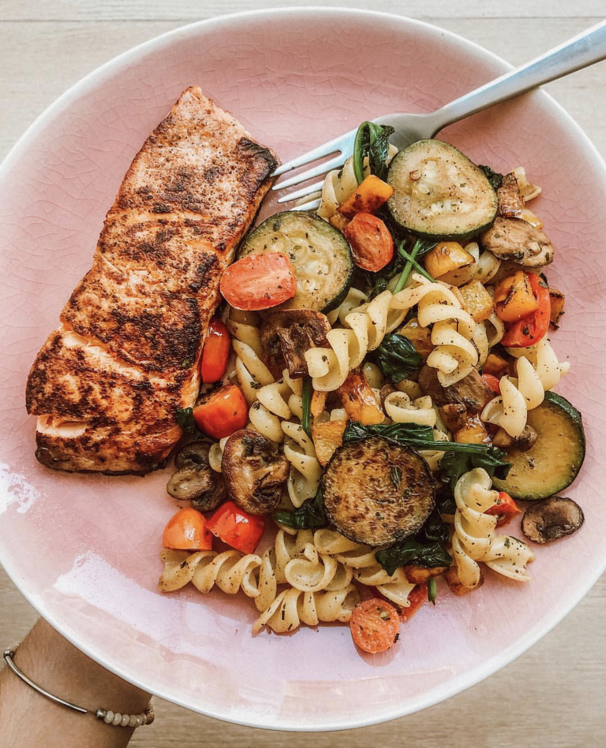 Plate with cooked salmon accompanied by pasta and vegetables.
