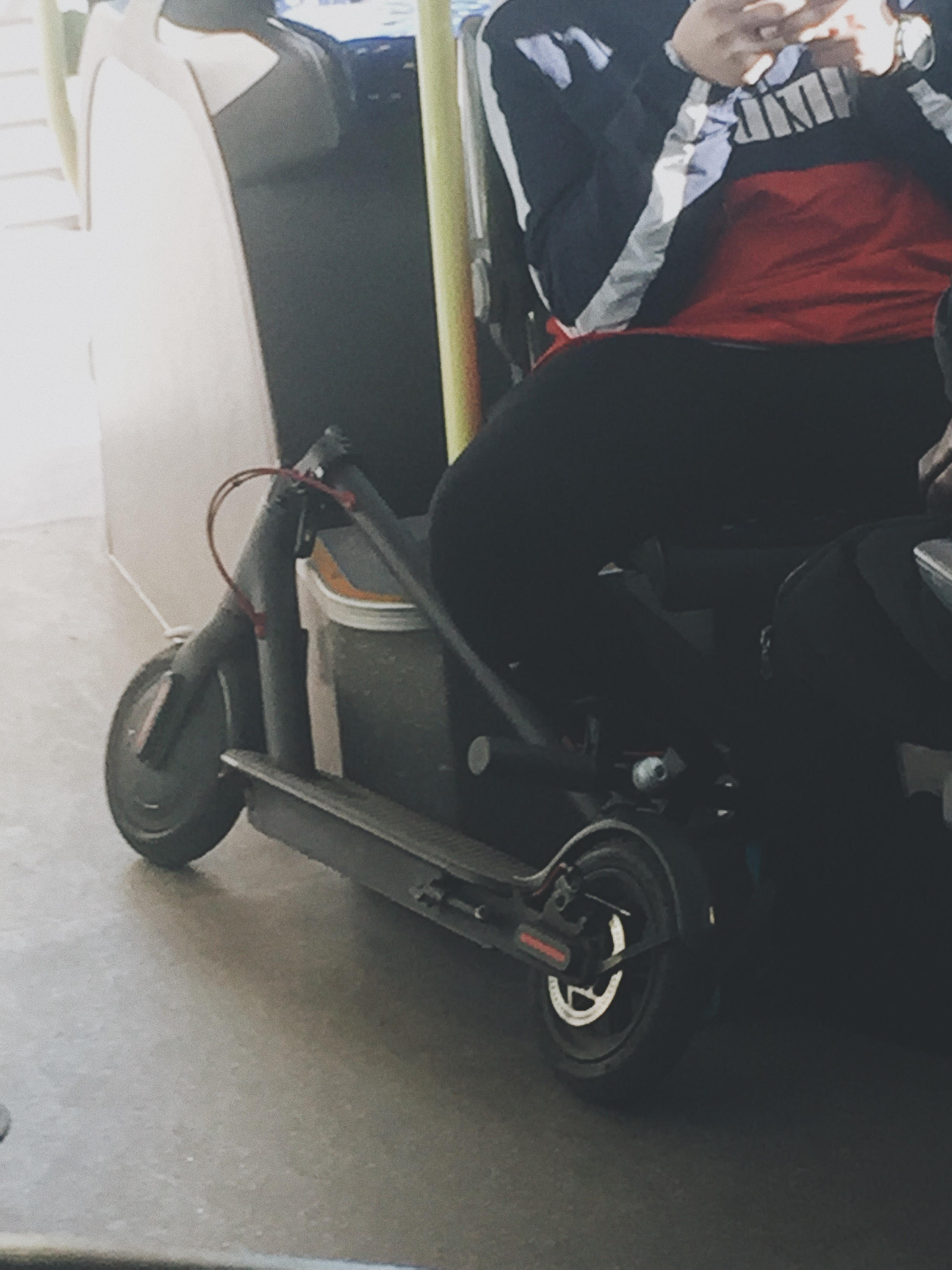 An electric scooter carried by a student inside a bus in Barcelona