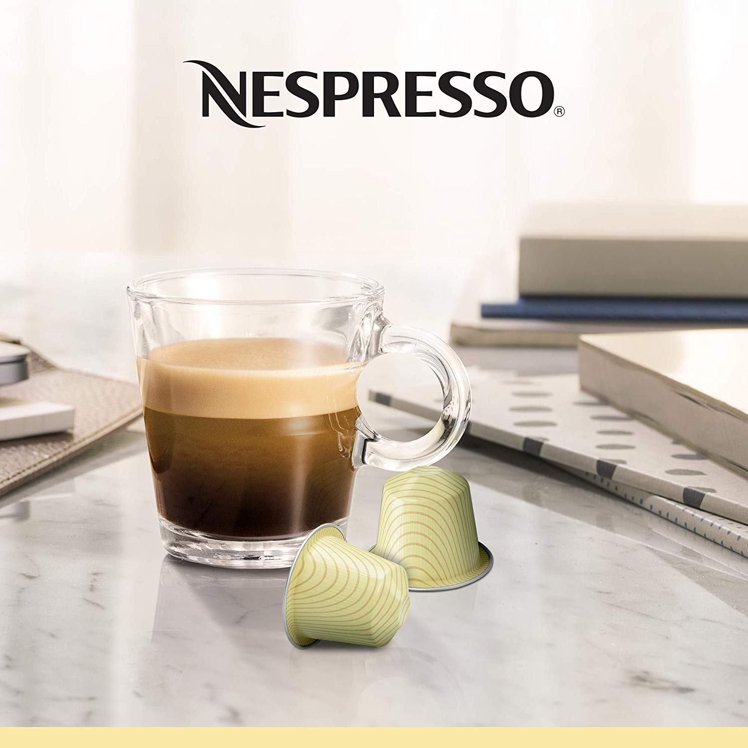 In this image you can see a glass of Vanilio coffee and accompanied with two coffee capsules